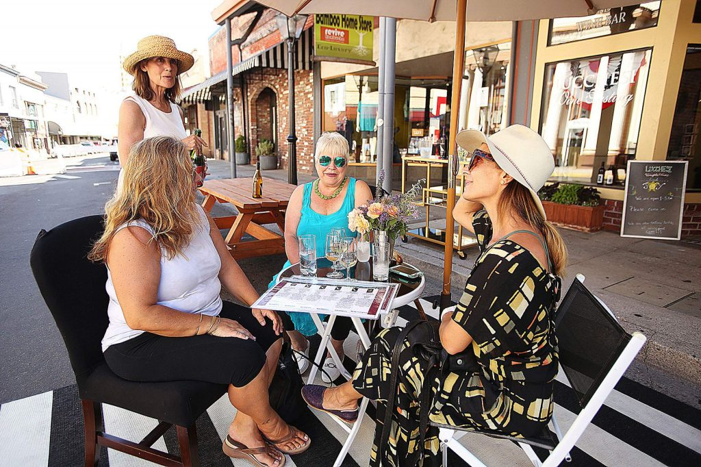 Family members Dixie Heart, Josephine Maniscalco, and Chrissie Gallegos are poured glasses of wine from Lucchesi Vineyards' Linda Clough Wednesday in downtown Grass Valley where Mill Street has been opened to foot traffic between Mill and Bank streets.