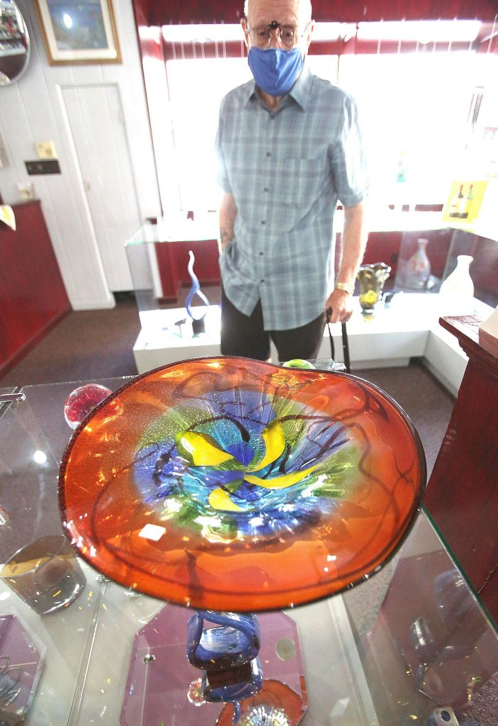 Nevada City Crystal & Glass' Peter Ray stands behind one of the many intricate and artistic glass designs available for purchase at the downtown Nevada City shop.