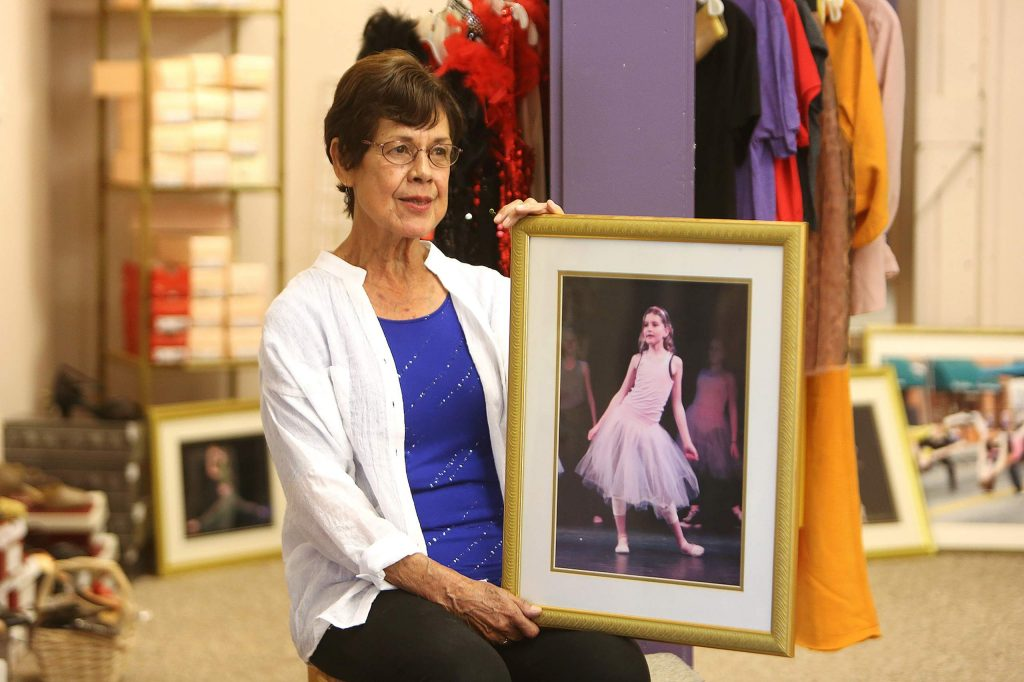 Delores Jones holds an image of one of the many dancers who have utilized her dance store shop over the decades.