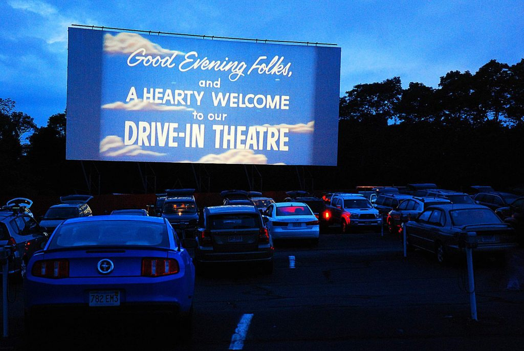 A drive in movie theater welcomes its guests to their outdoor theater before the start of their feature movie.