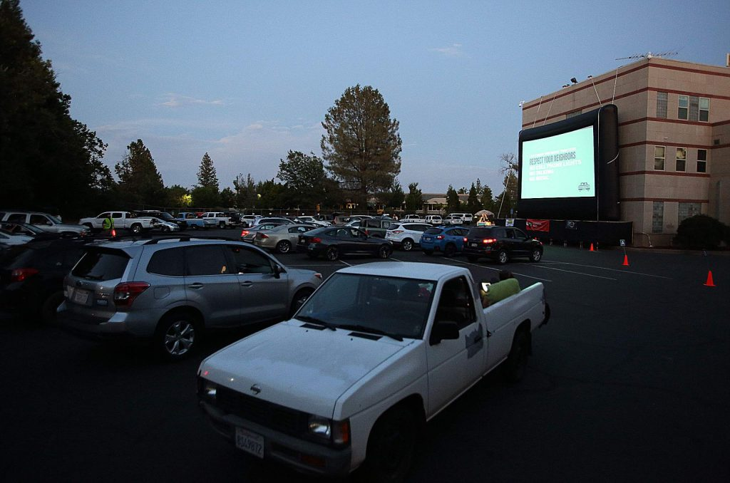 Vehicles are guided into the spaces set up outside of Grass Valley's Litton Building where the Movies Under the Pines: Drive In! movie showings are being held.
