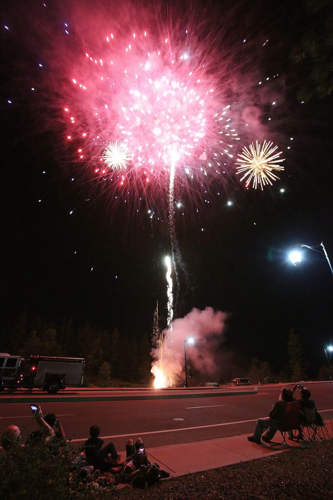 Spectators on the sidewalks take in Saturday's Fourth of July fireworks display.