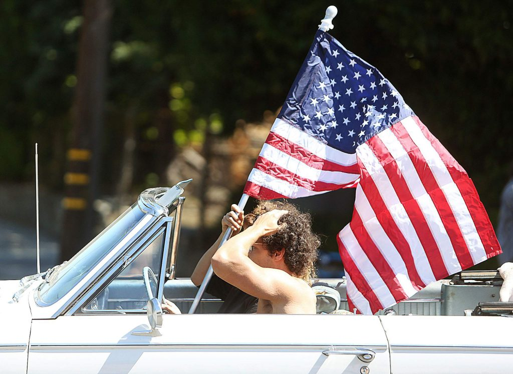 The stars and stripes are waved from the open cab of a classic convertible tagging along for part of Saturday's stay at home parade through Grass Valley and Nevada City.
