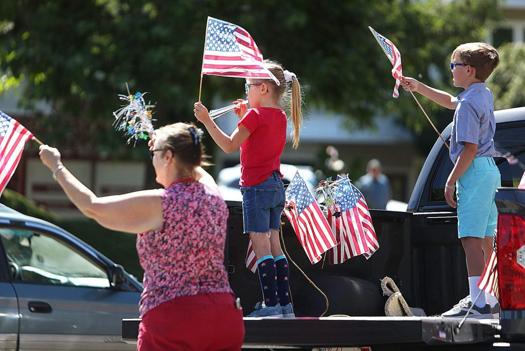 Families gathered along the stay at home parade route to wave on the Nevada City and Grass Valley first responders and service workers in Saturday's Fourth of July parade.