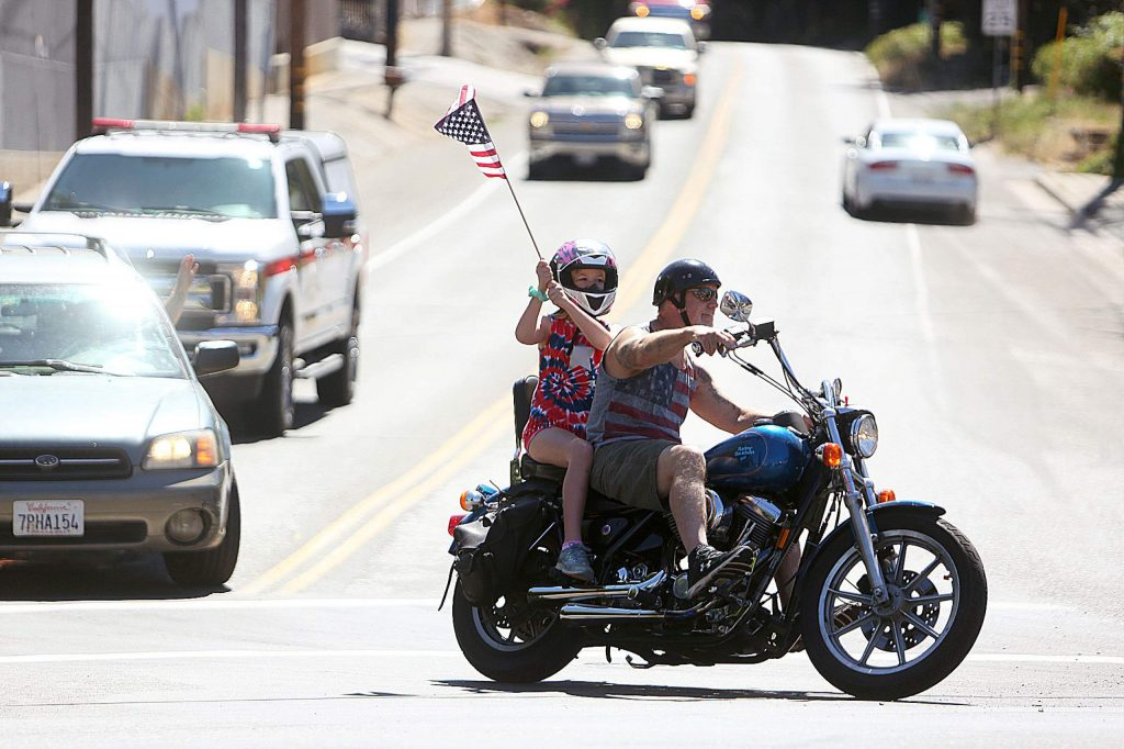 A motorcyclist with festively dressed rider makes the turn from Empire Street onto South Auburn during Saturday's Fourth of July parade.