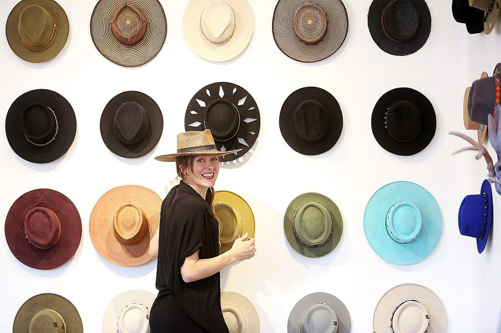 Jacqueline Michie stands in front of a wall of her custom made hats for sale at her shop, Mill And Main, at Mill and Main streets in downtown Grass Valley.