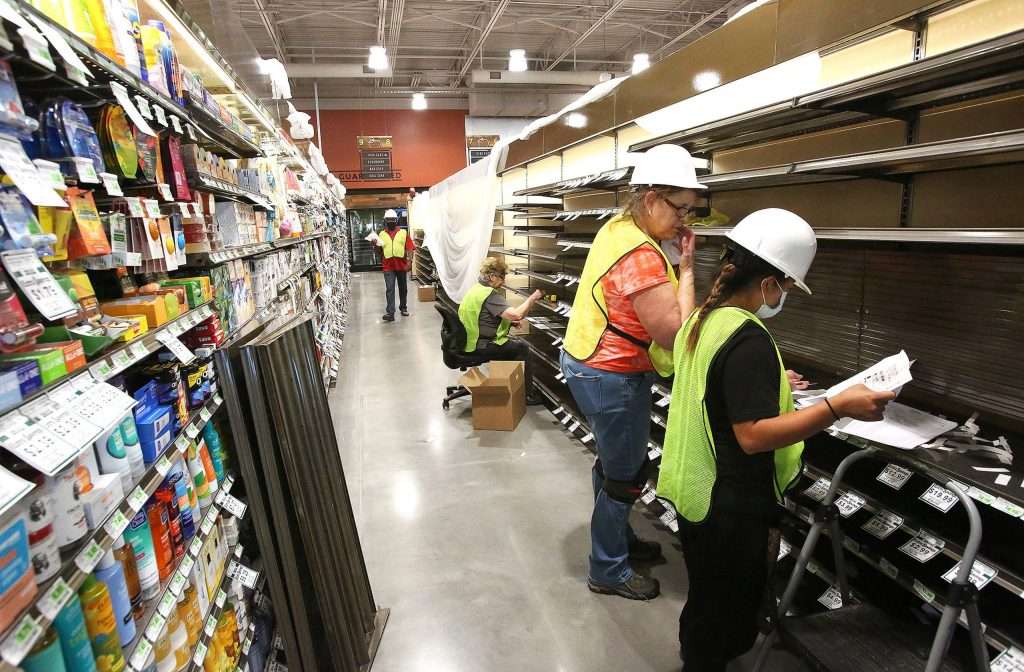 Construction workers inside of the new Higgins Marketplace Holiday Market work on building and stocking shelves with product Thursday in South County.
