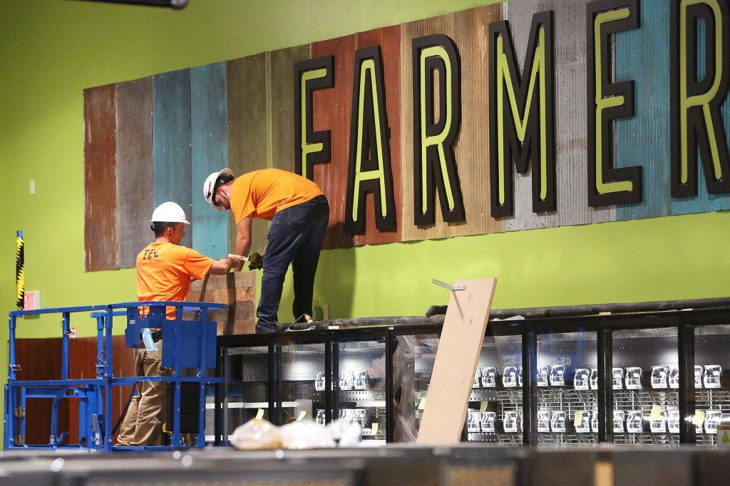 Construction workers are putting the finishing touches to the interior of the Higgins Marketplace Holiday Market.