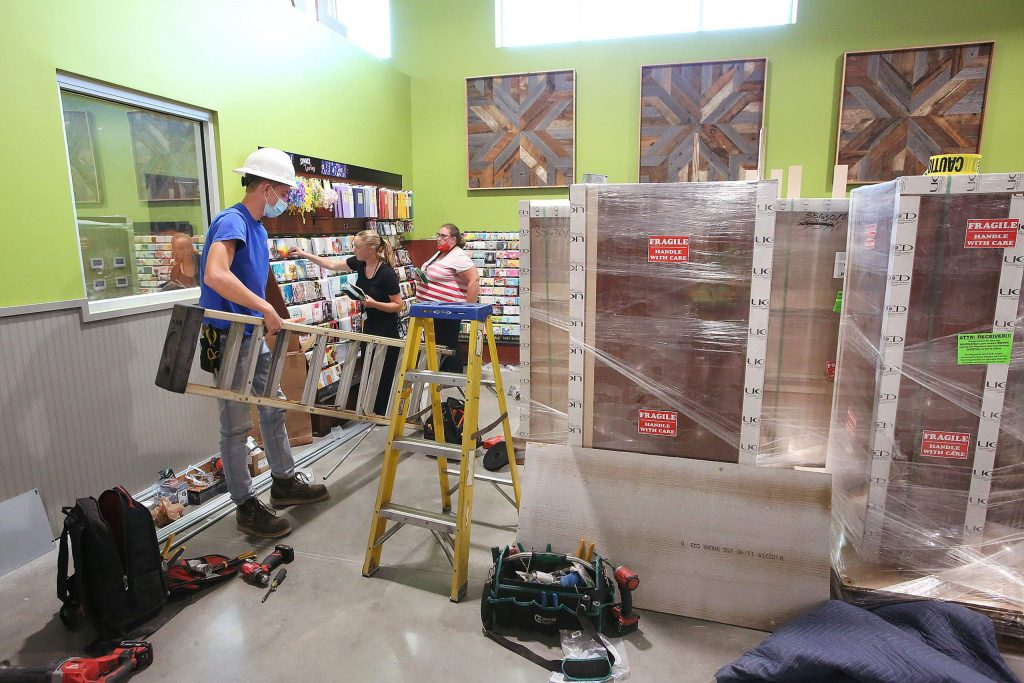 Construction crews work on building shelving while Holiday Market employees stock them with product as workers aim for their July 31 target opening date.