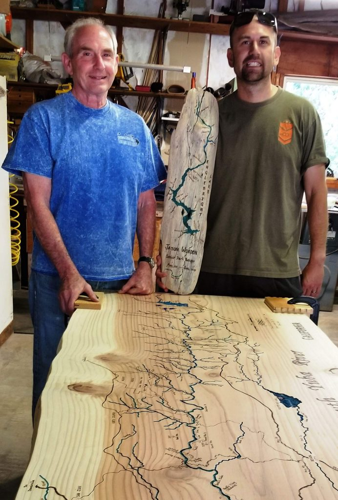 Pete Brost of Nevada City, left, engraves intricate renditions of the Yuba River Watershed. Jaime Ramirez is holding one of the plaques Brost created for the US Army Corps of Engineers at Englebright Lake.
