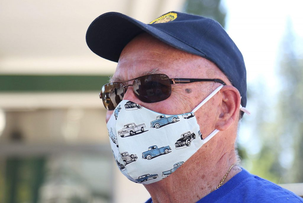 Nevada City Rotarian Mike Inglis shows off his mask featuring classic pickup trucks during Saturday's mask giveaway in Nevada City.