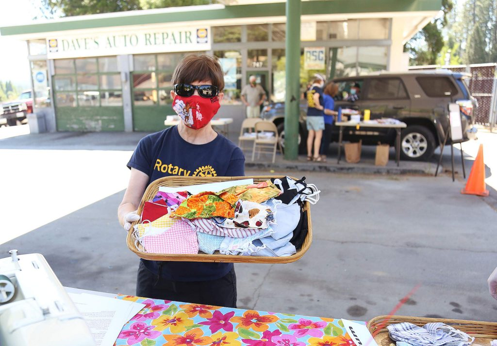 Nevada City Rotary Club member of 12 years, Robin Mylam, holds a display of face masks offered to folks driving in to Dave's Auto Repair in Nevada City for Saturday's free mask giveaway.