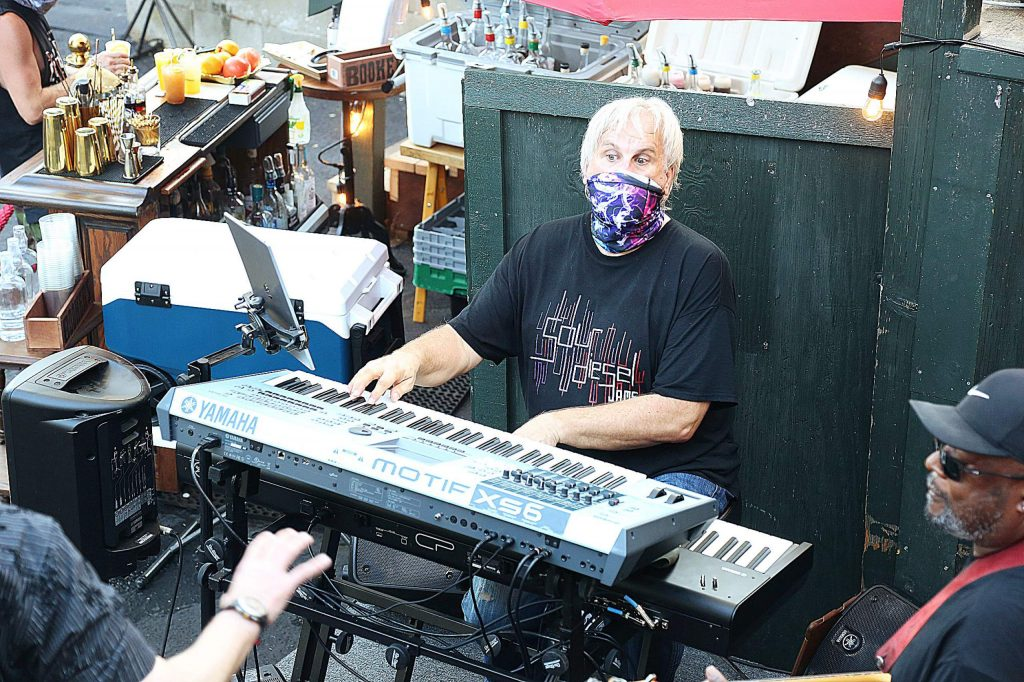 Ken Berger of the band Sour Diesel Jams dons his face covering while playing with the four piece ensemble Saturday night on the back patio stage recently constructed at The Golden Era.
