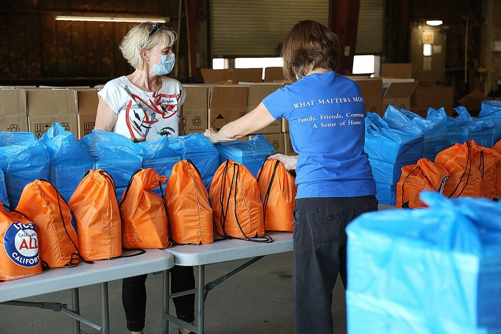 Volunteers help organize bags of personal protective equipment donated by the state government to be distributed to small businesses with under 25 employees. Each orange bag holds about one gallon of hand sanitizer, while the blue bags hold 450 surgical masks.