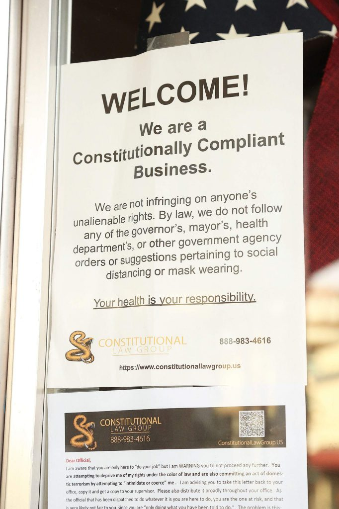 A notice near the front door of Old Town Cafe in downtown Grass Valley states that they are a constitutionally compliant business and that they choose not to follow the government's suggestions regarding social distancing or facial coverings.