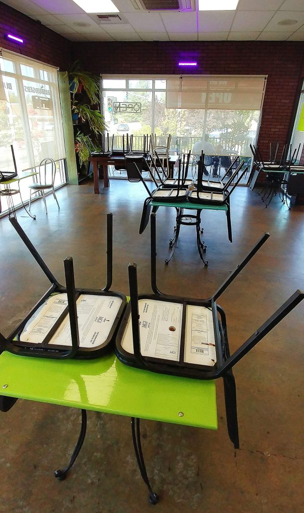 Seats are placed up on tables inside of Valentina's in Grass Valley's Glenbrook Basin while customers take their orders to-go Wednesday morning.
