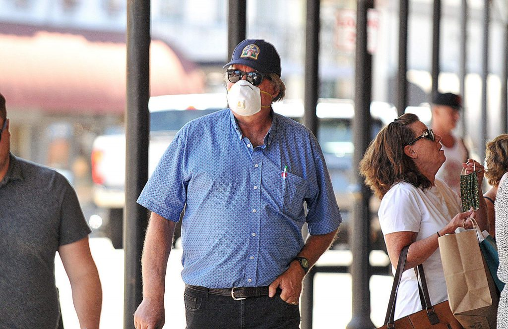 Congressman Doug LaMalfa dons a face covering while walking along Mill Street toward Old Town Cafe Tuesday afternoon, where a group of people met in opposition to the governor's recent orders to close indoor dining and bars.
