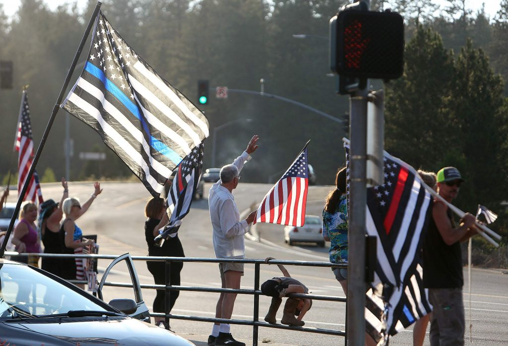 Back the Blue supporters wave flags at passing vehicles at Sutton Way and Brunswick Road Saturday afternoon.