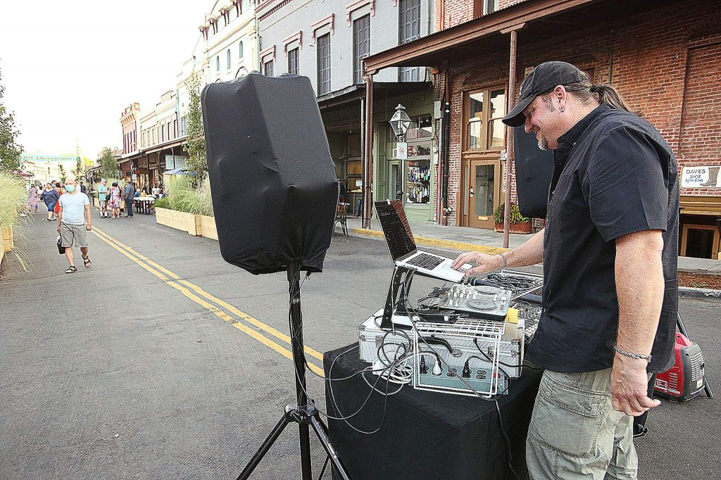 Disc jockey Steve Colby plays music for the Free Nevada County and downtown crowds gathered in between Sergio's Caffe and Old Town Cafe Saturday evening.
