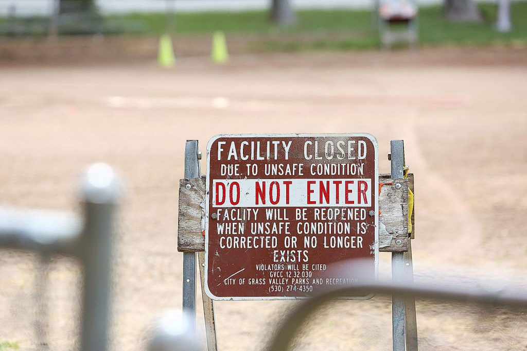 Multiple signs at Memorial Park's Les Eva Field remind those that it is not safe to enter.