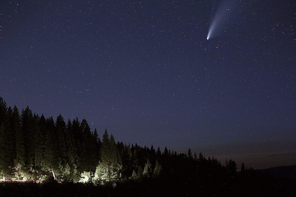 Vehicle traffic makes its way along Highway 20 east of Nevada City while the comet Neowise makes its way along the northwestern skyline as viewed from the Jefferson Creek Scenic Overlook.