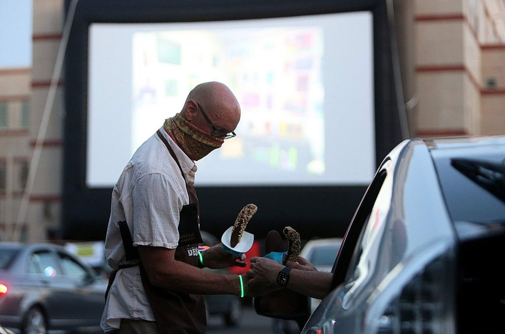 Concessions workers bring Cheri's Hand Dipped Ice Cream to a guest in a car while the Nevada City Film Festival's Drive-In theater movie nights commenced mid July.