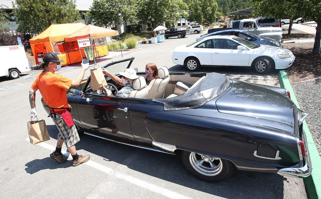 Auburn's John and Betty Martin receive a pair of meals from Kalikos Hawaiian Grill from the comfort of their 1950 Studebaker during the final Nevada County Car Hop event held in the parking lot of the Eric Rood Administrative Center.