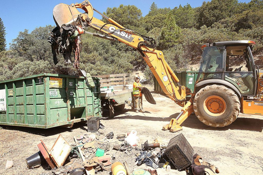 A backhoe is used to load trash from the homeless camps into a bin during Wednesday's cleanup on Sugarloaf Mountain.