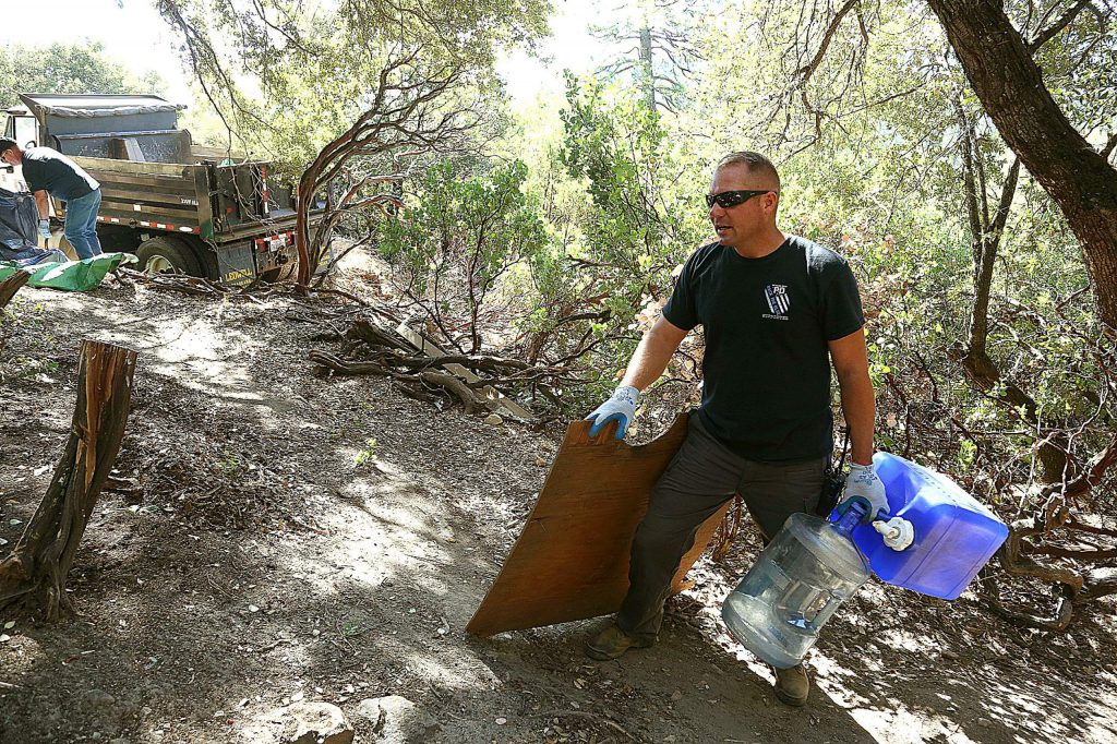 Nevada City Police Chief Chad Ellis helps out with the Sugarloaf encampment clean up Wednesday morning.