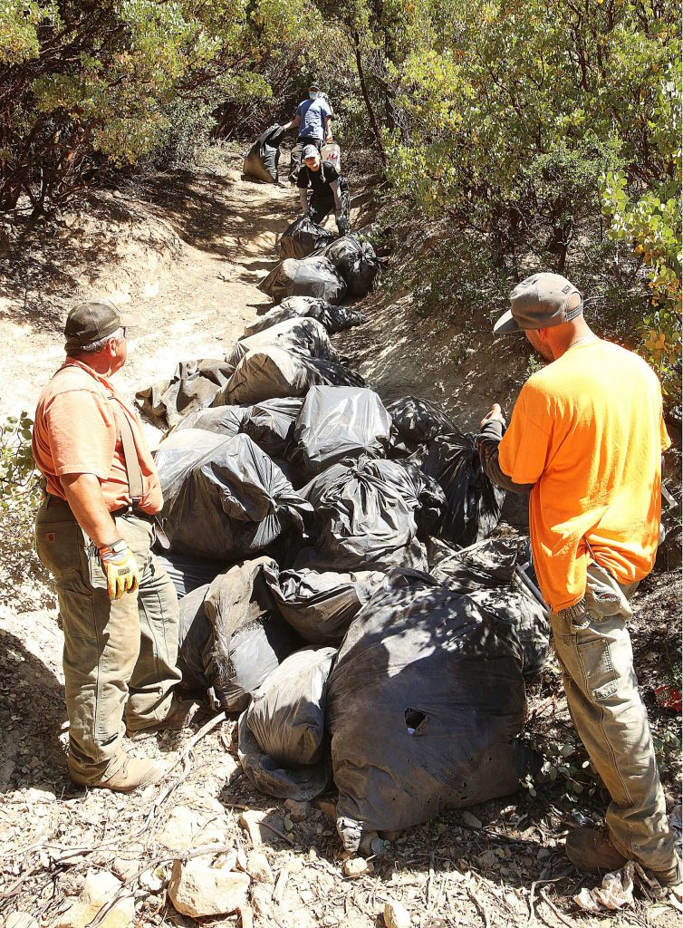 Bag after bag full of refuse pulled from the Sugarloaf Mountain homeless encampments is rolled down the trail until they can be put into garbage dumpsters.