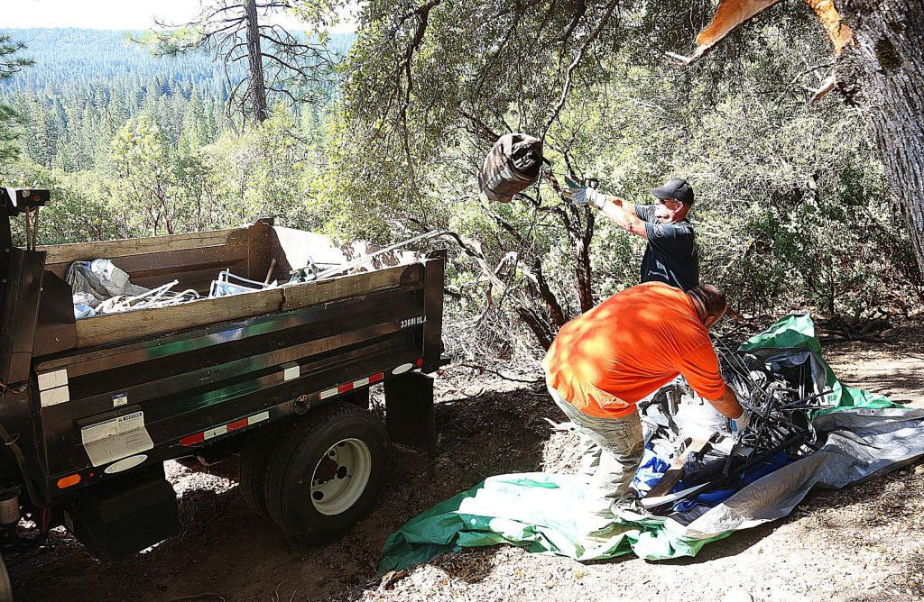 Nevada City employees throw refuse into the back of a dump truck during a community cleanup day of the Sugarloaf Mountain homeless camps Wednesday morning.