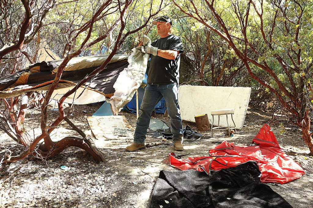 Nevada City Police Lt. Paul Rohde helps with Wednesday's cleanup. Homeless people from these encampments have been temporarily housed at the Northern Queen.