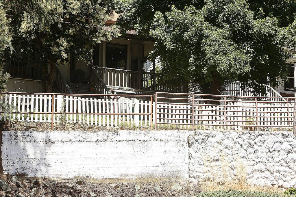"""A spray painted message of """"go home"""" has been covered with white paint on a portion of a retaining wall along the 300 block of Mill Street in Grass Valley, where a row of small Confederate flags were also placed over the Fourth of July holiday."""