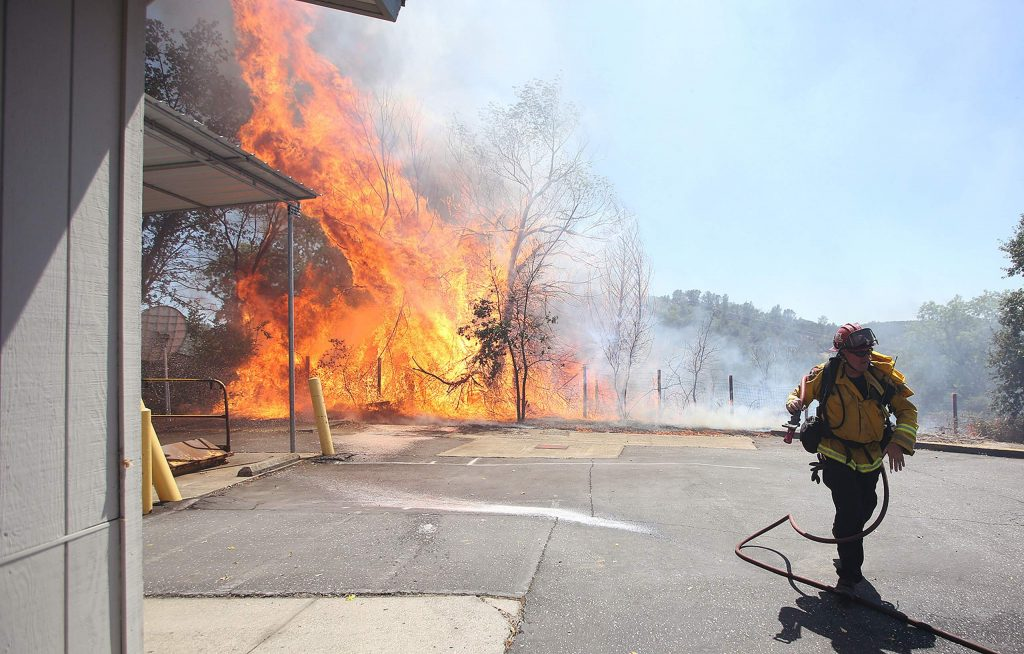 A firefighter works swiftly to protect the Smartsville Post Office and other structures threatened during the Smartsville Fire, which burned approximately 6 acres Thursday afternoon.