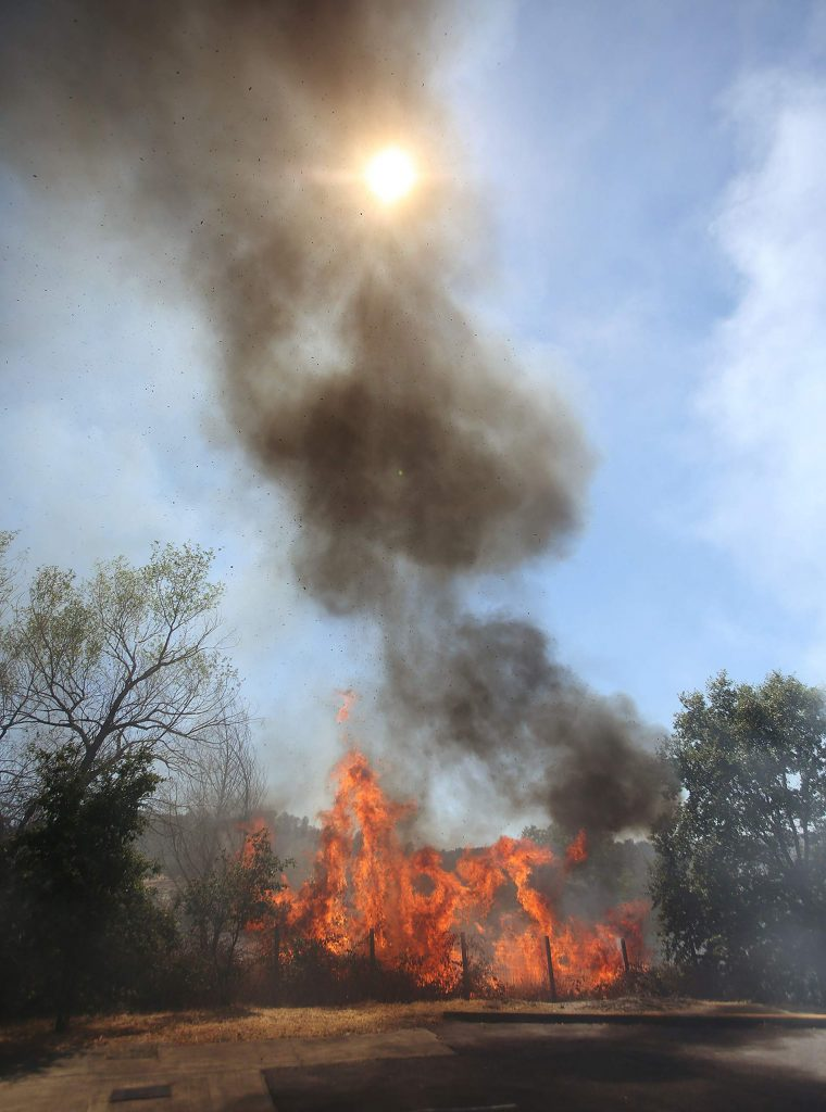 Flames from a flare up of the Smartsville Fire threaten nearby structures off Smartsville Road in Yuba County Thursday. Fire danger in Northern California remains high as high temperatures soar for the next few days.