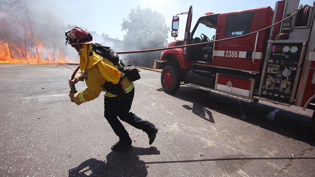 A firefighter begins an attack on a spot fire, part of the Smartsville Fire Thursday in Yuba County. The forward progress of the fire was held at 6 acres.