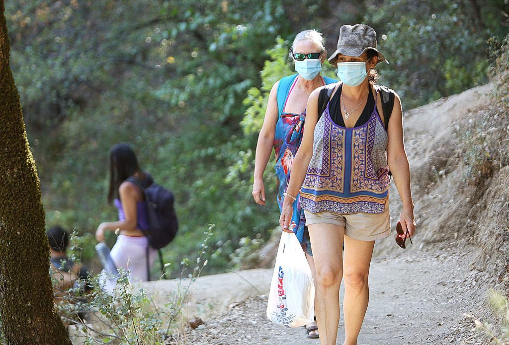 Grass Valley's Nancy Moore and Prema Robins don their face masks as they hike the narrow trails of the South Yuba River State Park while en route to a swimming hole. More people are using face coverings while walking along the paths or have them ready to use when other parties approach.