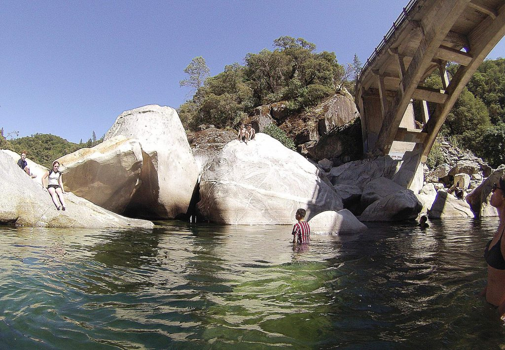 A family from Marin County use the rocks of the South Yuba River to sit and jump off of this week under the Highway 49 bridge.