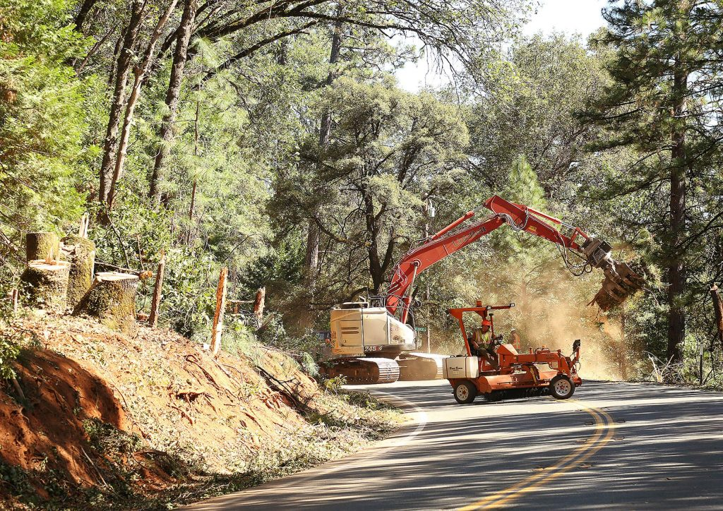 Caltrans workers use equipment to help clear vegetation from the Highway 174 right-of-way being widened for efforts to make the roadway safer.