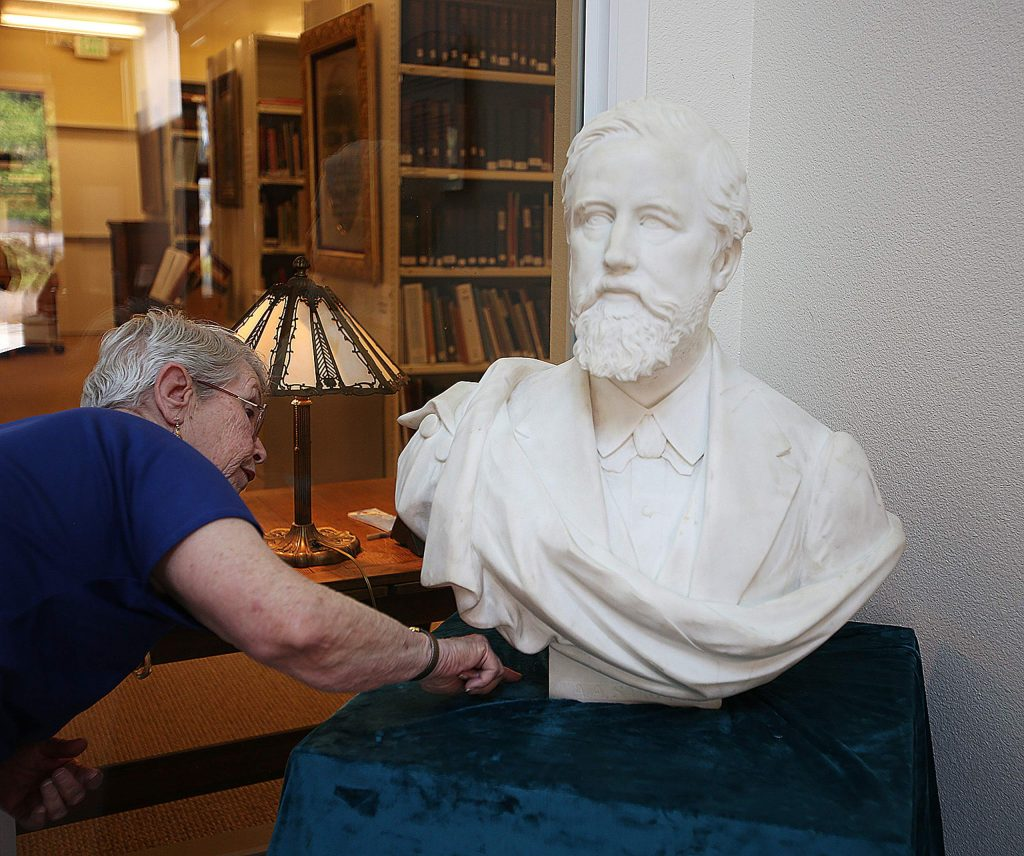 Searls Historical Library's Pat Chestnut points to where the sculptor left his mark on the 1876 bust of A A Sargent, by P. Mezzara.