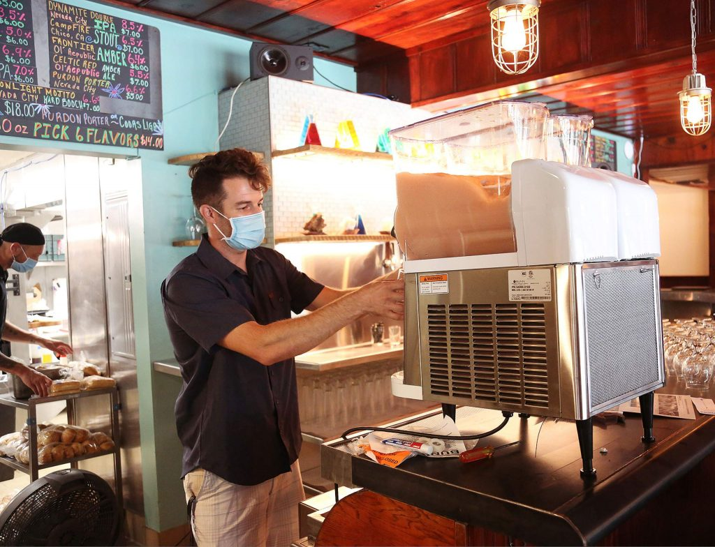 Co-owner of the Wheelhouse, Max Norskog, pours a glass of NC Kombuchary and Gold Vibe Hard Kombucha from the first known slushie kombucha dispenser.