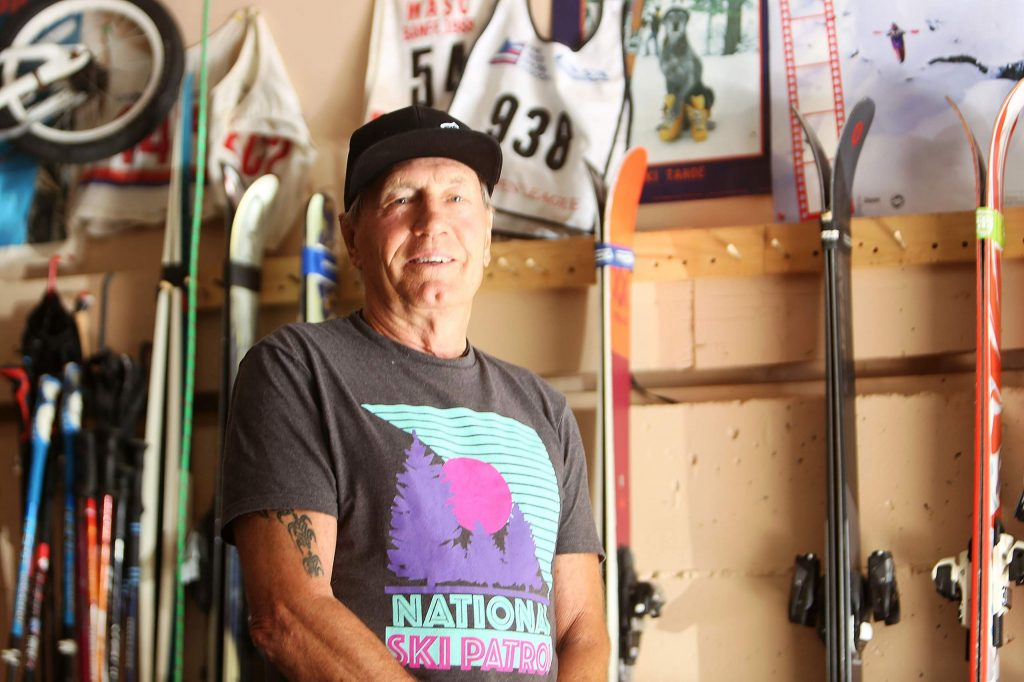 Nevada City's Don Attix stands in front of his garage wall full of pairs of skis as well as memorabilia he's collected along his decades of staying active on the mountains.