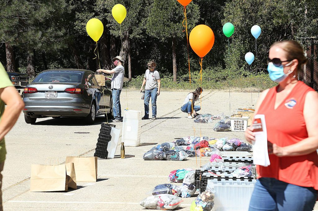 Volunteers for The Karing Closet of Nevada County tend to participants in the drive-thru clothes giveaway Saturday at the Telestream parking lot in Nevada City.