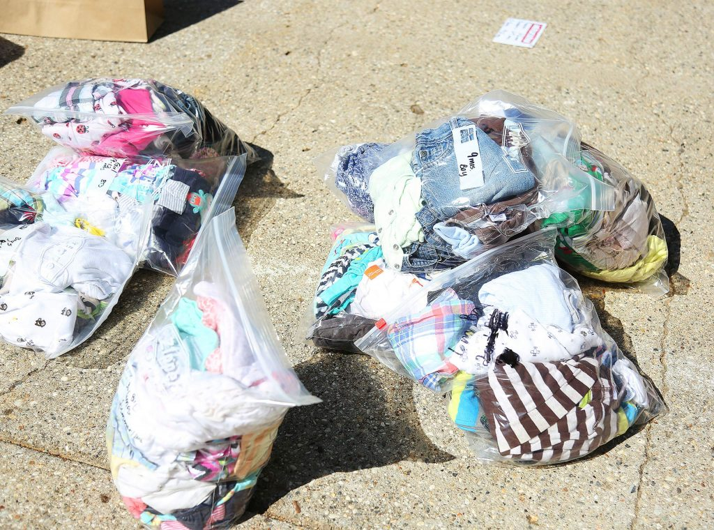 """Pre sorted, bagged and clean clothes, await their new owners during Saturday's """"growth spurt giveaway"""" of apparel for kids age 0 and up."""