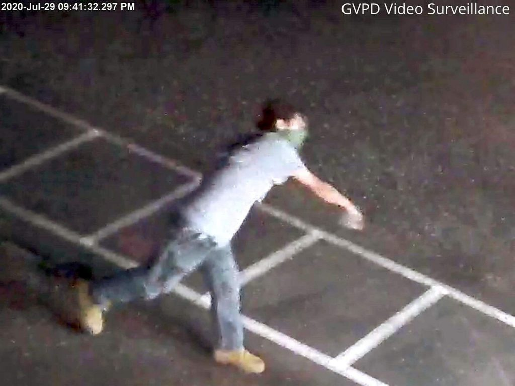 Surveillance video captured the suspect throwing a rock through the door of the police department.