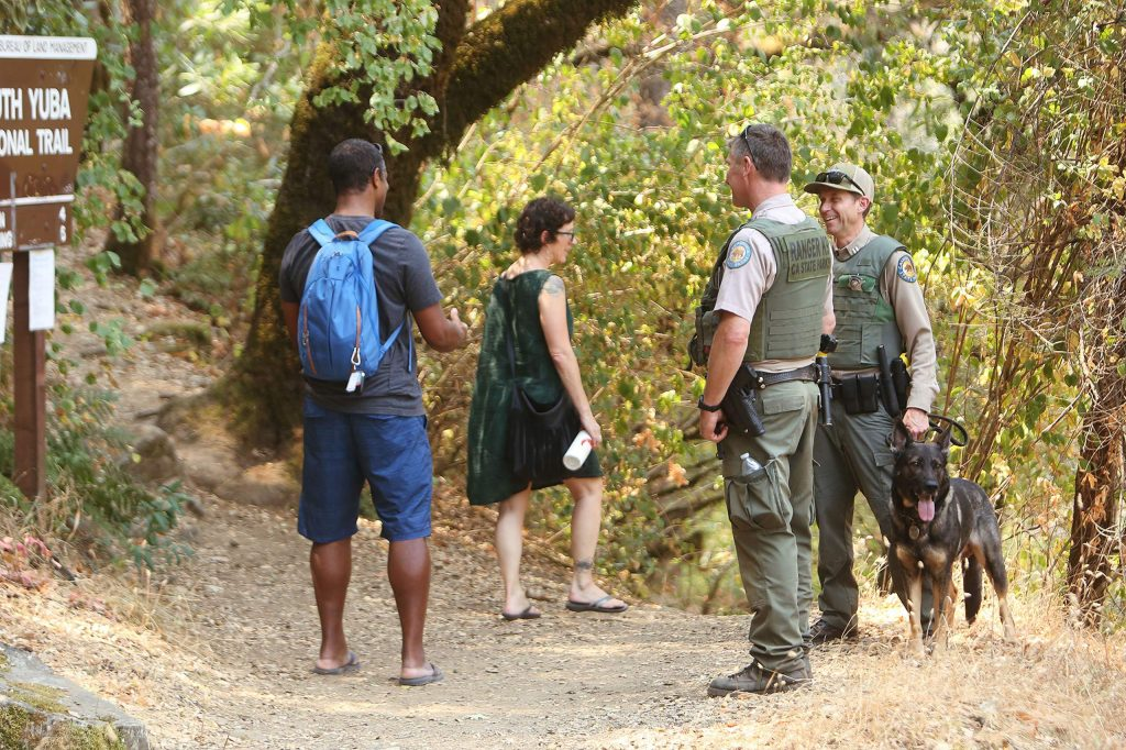 State Parks Rangers Martin Gilbertson and Mike Gleckler with K-9 unit Armin, greet a pair of South Yuba River visitors Saturday at Edwards Crossing. The officers were part of a collaborative effort with CHP, Nevada County Sheriff's Office, Nevada County Consolidated Fire, California State Parks and Cal Fire to curtail unsafe conditions including illegal parking, littering, graffiti, and DUI enforcement.