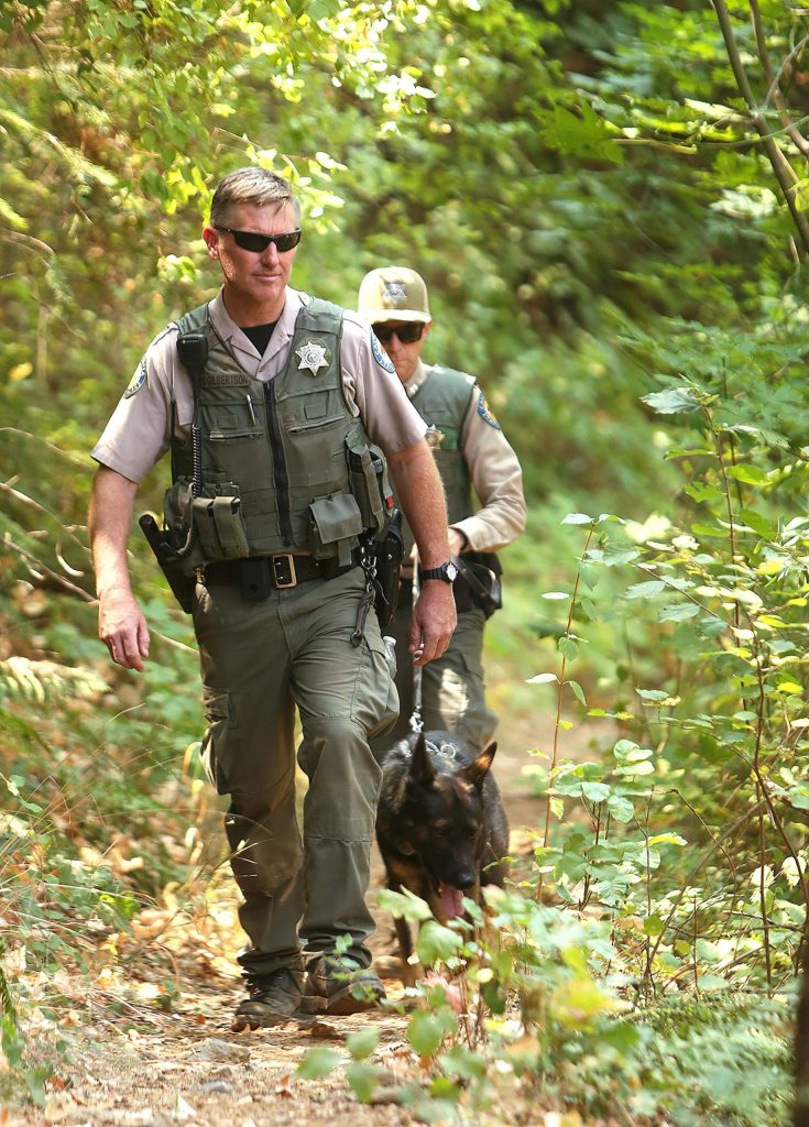 State Parks Rangers Mike Gleckler with K9 Armin, and Martin Gilbertson, keep an eye on folks using the river from the South Yuba Trail Saturday at Edwards Crossing, part of a collaborative effort to curb illegal activity.