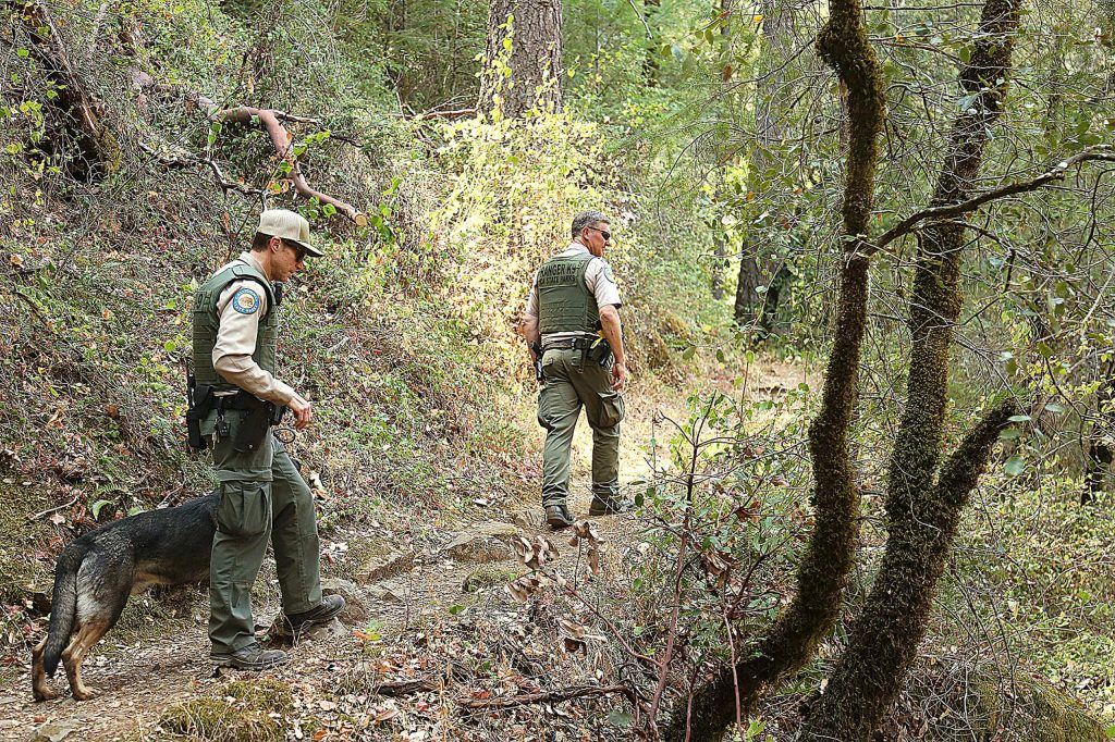 State Parks Rangers Mike Gleckler with K-9 Armin, and Martin Gilbertson, keep an eye on those visiting the river from the South Yuba Trail Saturday at Edwards Crossing, part of a collaborative effort to curb illegal activity.