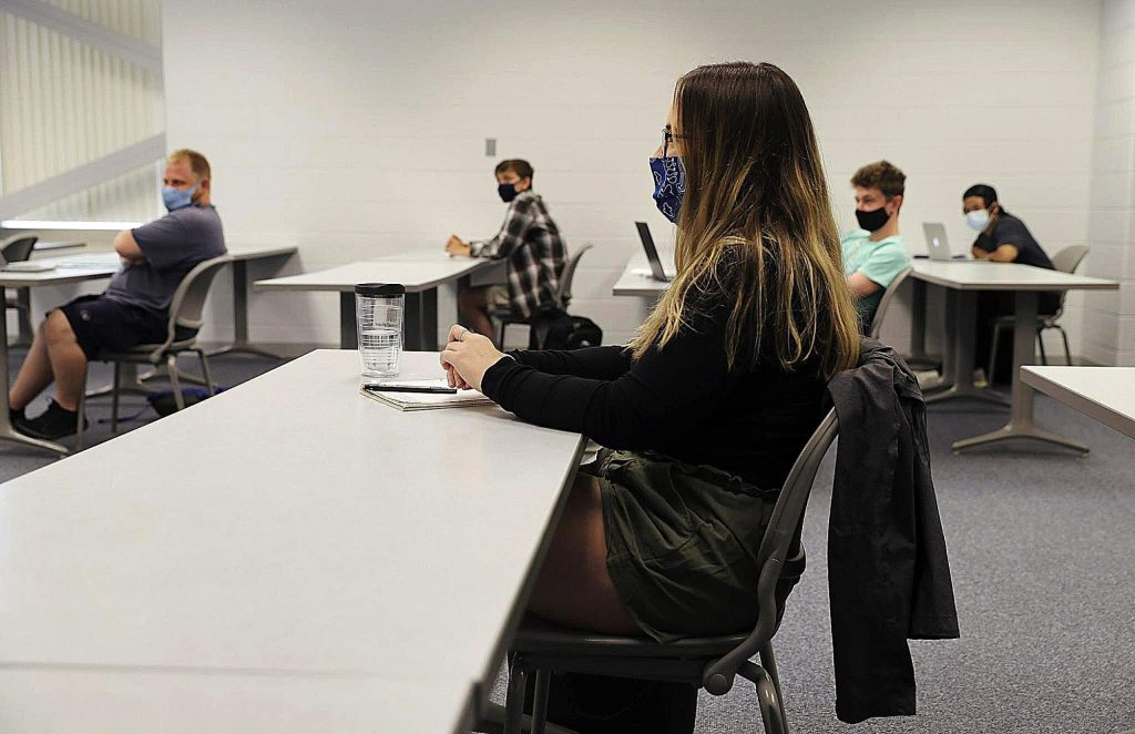 Students sitting one per row on each side of the room and wearing face masks, listen to instructor Robert Gynn, during a speech class at College of Lake County in Grayslake, Ill., Thursday. Six students were present, with a room capacity for nine.