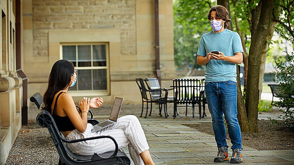 Bryan Maley, right, a grad student in the Master of Public Health program, interviews a student on campus about mask-wearing experiences as part of a public health survey, Friday in Ithaca, N.Y.